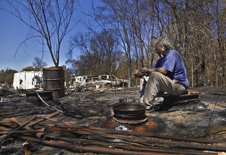 Andrew Wood takes a break from going through the damage on his family's property left behind on Tuesday, Sept. 6, 2011, in Oklahoma City, Okla. after the wildfires that cut a path through northeast Oklahoma City last week.  Photo by Chris Landsberger, The Oklahoman