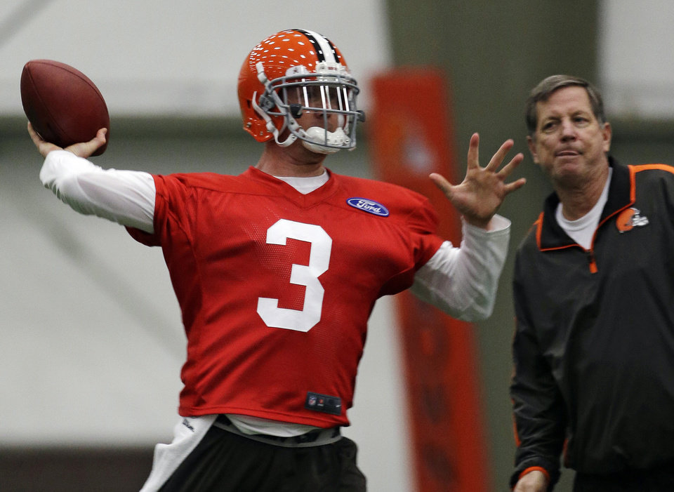 Photo - Cleveland Browns quarterback Brandon Weeden throws during NFL football mini-camp at the team's training facility, Tuesday, April 16, 2013, in Berea, Ohio. Weeden and Jason Campbell threw passes side-by-side as the Browns opened their first mini-camp of the season. The 29-year-old Weeden is the incumbent and started 15 games last year. He was the 22nd overall pick in the 2012 draft. Campbell, 31, was signed as a free agent on March 26. The ninth-year pro appeared in six games last season with the Bears. (AP Photo/Tony Dejak)