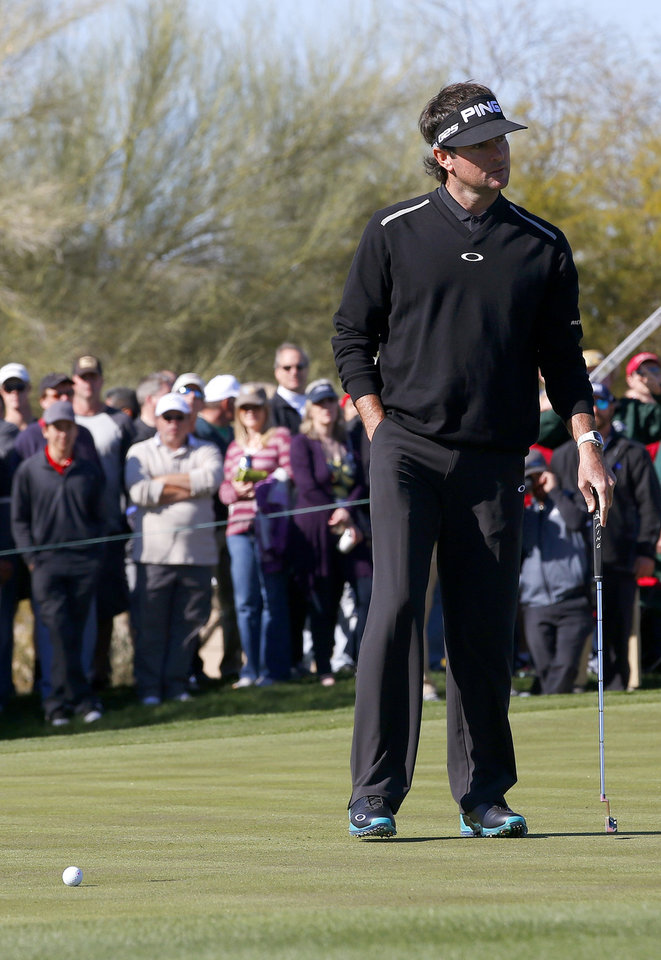 Photo - Bubba Watson looks over at his caddie after missing a birdie putt on the second hole during the final round of the Phoenix Open golf tournament on Sunday, Feb. 2, 2014, in Scottsdale, Ariz. (AP Photo/Ross D. Franklin)