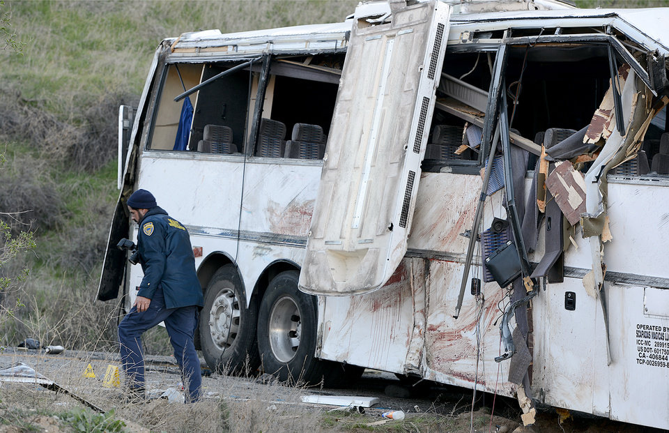 Authorities work Monday Feb. 4, 2013, at the scene of Sunday\'s fatal tour bus crash on Highway 38 north of Yucaipa, Calif., that left at least eight people dead and dozens injured. The cause of the Sunday crash east of Los Angeles remained under investigation. (AP Photo/The Sun, Rick Sforza)