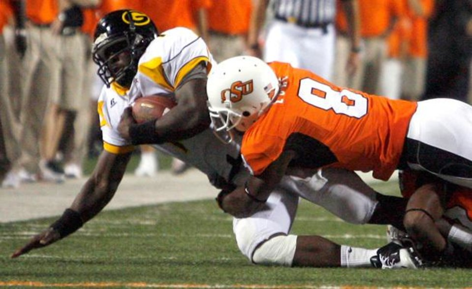 Photo - Daytawion Lowe (8) tackles Grambling quarterback Greg Dillion (1) during the college football game between the Oklahoma State University Cowboys (OSU) and the Grambling State University Tigers (GSU) at Boone Pickens Stadium in Stillwater, Okla., Saturday, September 26, 2009. Photo by Sarah Phipps, The Oklahoman