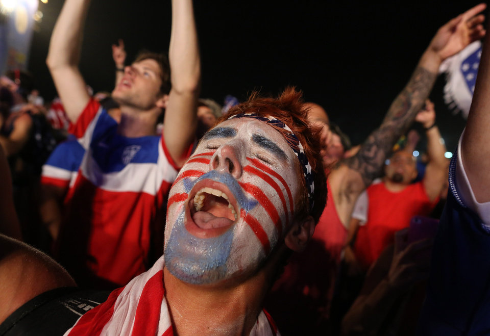 Photo - A fan of the U.S. national soccer team celebrates his team's victory during a live broadcast of the soccer World Cup match between the Unites States and Ghana, inside the FIFA Fan Fest area on Copacabana beach, Rio de Janeiro, Brazil, Monday, June 16, 2014. Clint Dempsey scored in the first minute and rookie substitute John Brooks scored a late game winner as the U.S. defeated Ghana 2-1 in the World Cup opener for both. (AP Photo/Leo Correa)