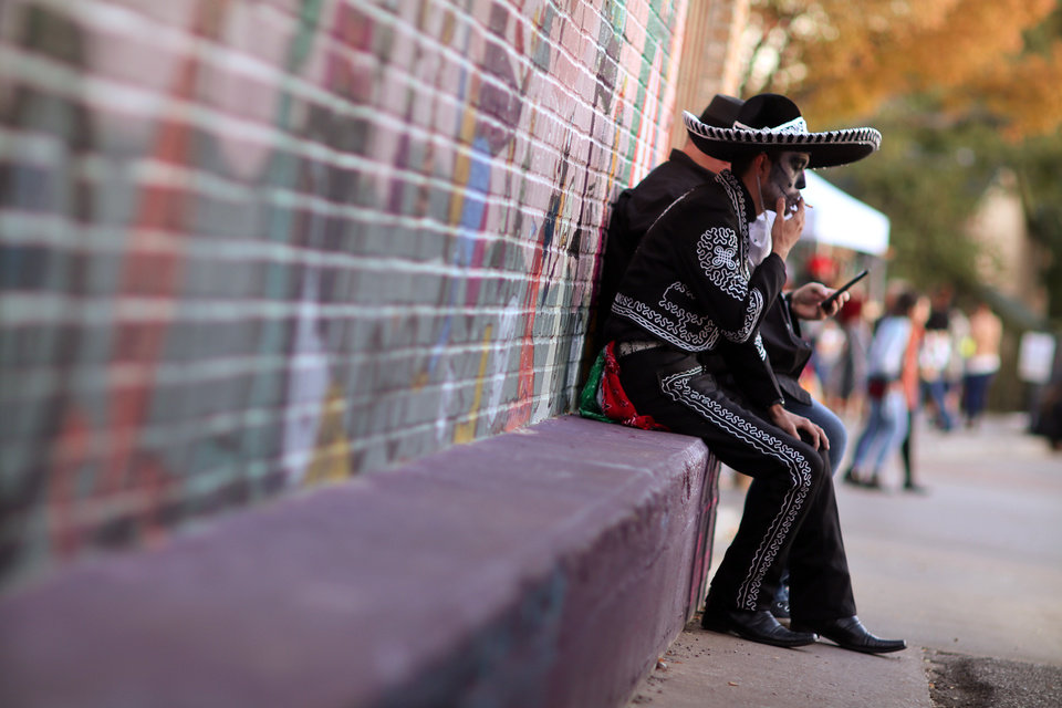 Photo - THE OK Magazine. Erich Eberle catches a smoke during the Day of the Dead festival in the Plaza District Sunday, November 3, 2019. Photo by Doug Hoke