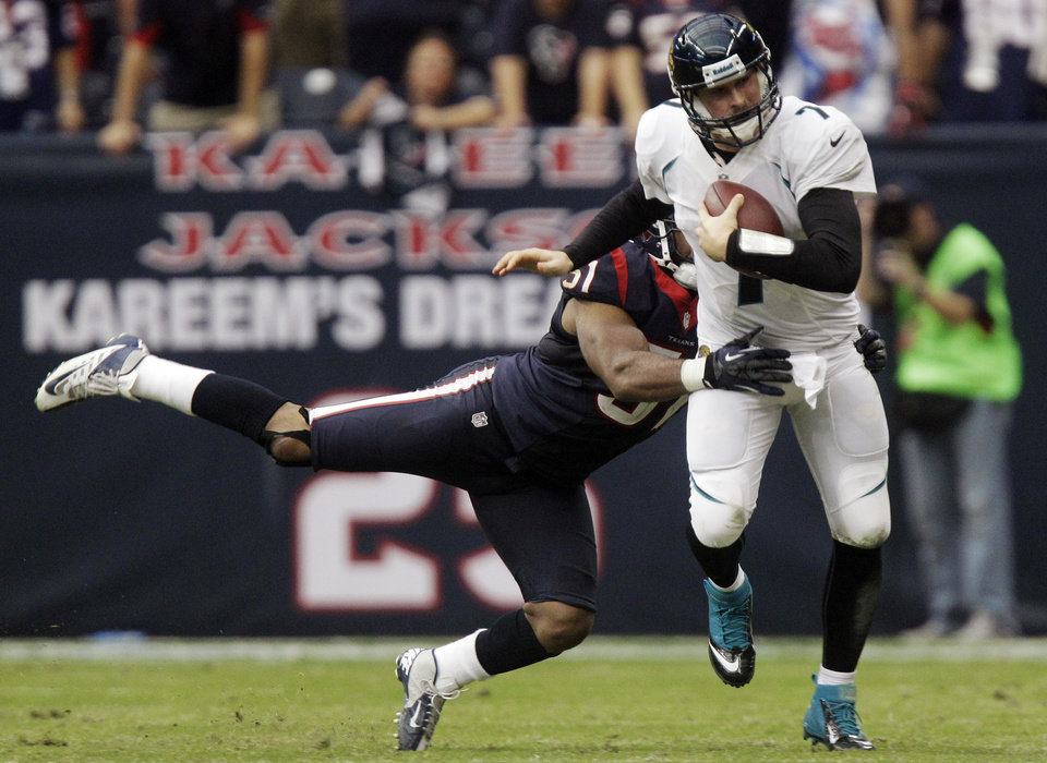 Photo -   CORRECTS TEXANS PLAYER TO DARRYL SHARPTON (51), SHILOH KEO (31) - Jacksonville Jaguars quarterback Chad Henne (7) breaks a tackle by Houston Texans' Darryl Sharpton (51) in overtime of an NFL football game, Sunday, Nov. 18, 2012, in Houston. The Texans won 43-37. (AP Photo/Patric Schneider)