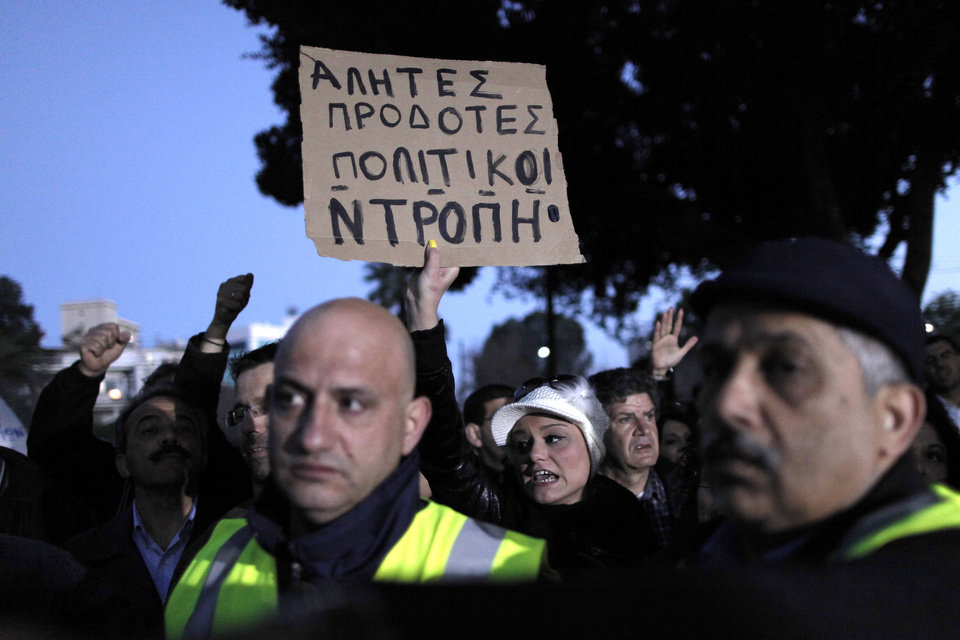 Photo - A bank employee holds a placard that reads in Greek: ''Bums, Traitors, Politicians, Same'' protest on Saturday, March 23, 2013. Thousands of bank employees took part in a protest that ended outside the Cypriot parliament. Politicians in Cyprus were racing Saturday to complete an alternative plan raising funds necessary for the country to qualify for an international bailout, with a potential bankruptcy just three days away. (AP Photo/Petros Giannakouris)
