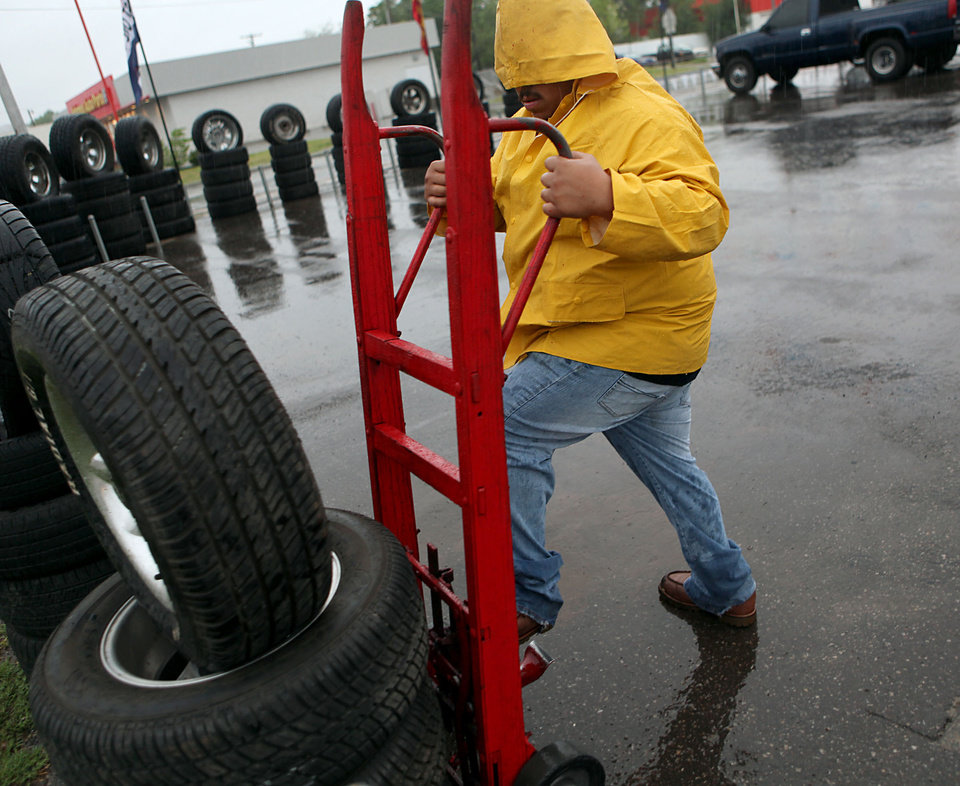 An employee of E&E Tires and Wheels in southeast Oklahoma City sets out tires in the rain on Wednesday, April 29, 2009. Photo by John Clanton