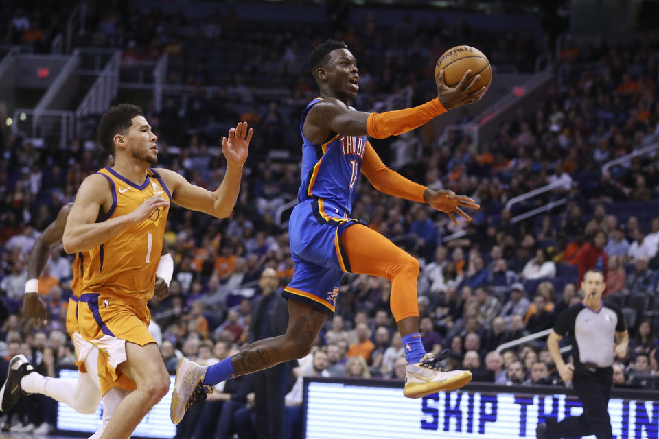 Photo - Oklahoma City Thunder guard Dennis Schroeder (17) drives past Phoenix Suns guard Devin Booker (1) during the first half of an NBA basketball game Friday, Jan. 31, 2020, in Phoenix. (AP Photo/Ross D. Franklin)