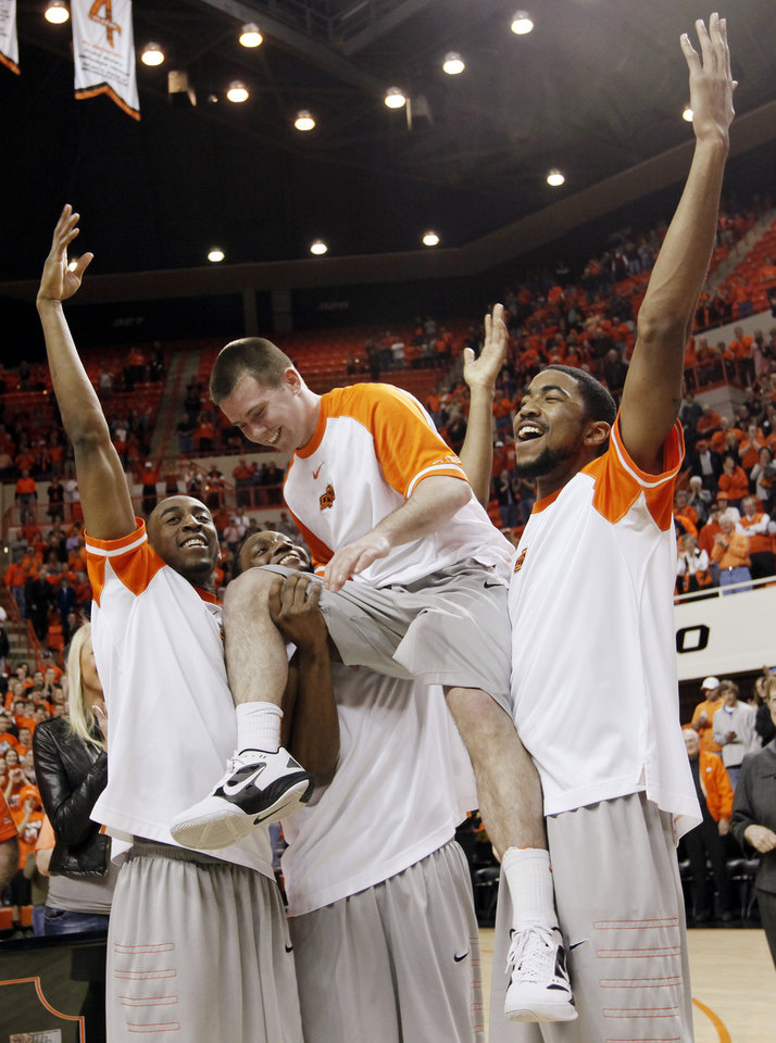 Photo - From left, OSU's Markel Brown, Brian Williams and Michael Cobbins hold up Keiton Page during senior day before a men's college basketball game between the Oklahoma State University Cowboys and the University of Kansas Jayhawks at Gallagher-Iba Arena in Stillwater, Okla., Monday, Feb. 27, 2012. Photo by Nate Billings, The Oklahoman