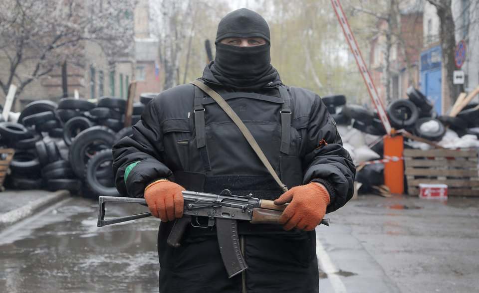 Photo - A pro-Russian gunman stands guard at a seized police station in the eastern Ukraine town of Slovyansk on Sunday, April 13, 2014. Pro-Moscow protesters have seized a number of government buildings in the east over the past week, undermining the authority of the interim government in the capital, Kiev. (AP Photo/Efrem Lukatsky)