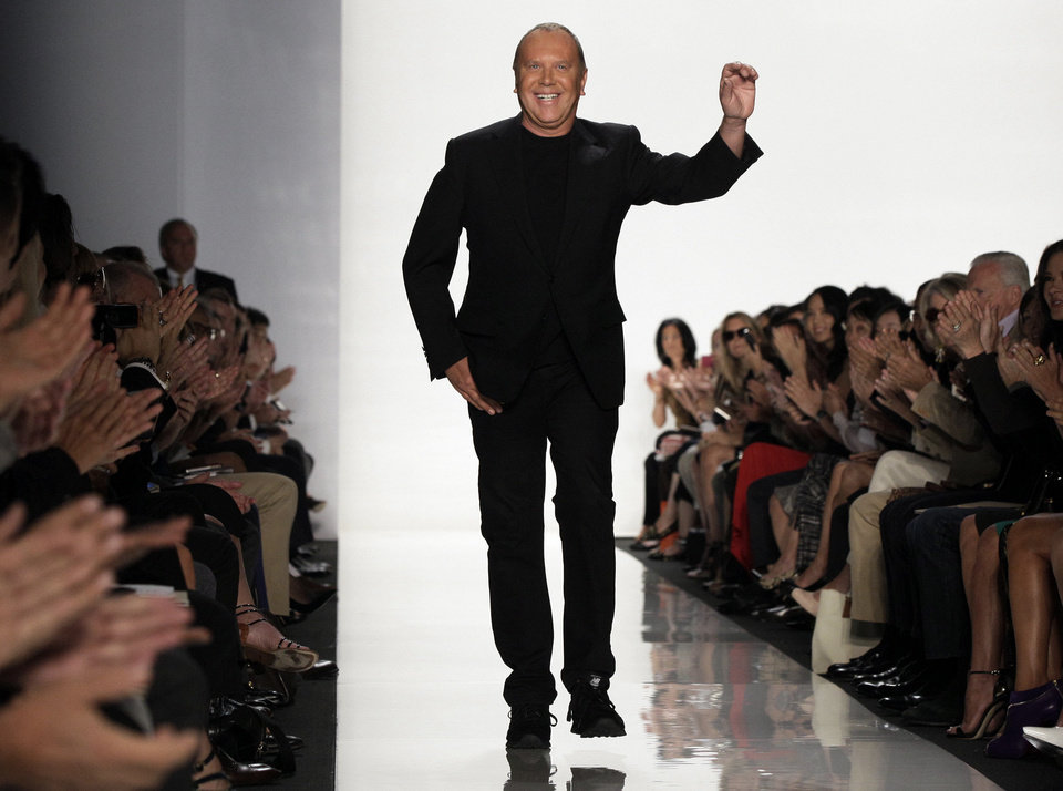 Photo - Designer Michael Kors acknowledges applause after his Spring 2013 collection was modeled during Fashion Week in New York.  Richard Drew - AP