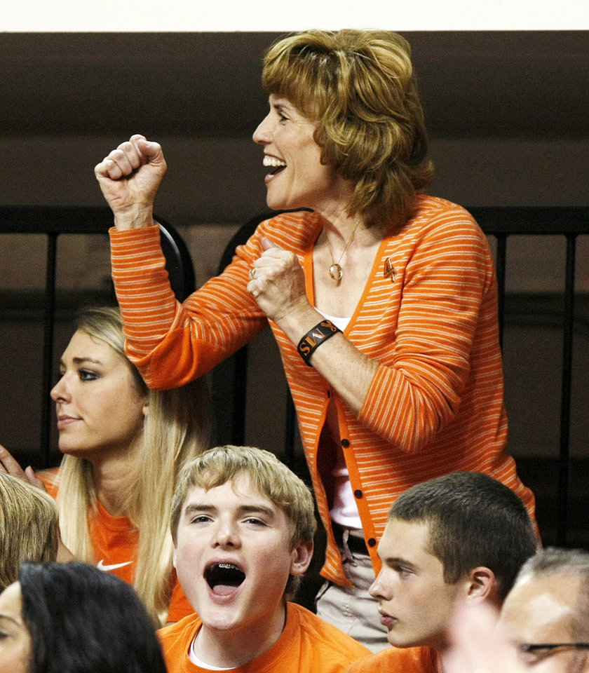 Shelley Budke, widow of OSU head coach Kurt Budke, cheers next to daughter Sara Budke, left, and son Brett Budke, cheering at lower left, during the Women's NIT championship college basketball game between Oklahoma State University and James Madison at Gallagher-Iba Arena in Stillwater, Okla., Saturday, March 31, 2012. Kurt Budke and three others were killed in a plane crash on a recruiting trip in November of 2011. Photo by Nate Billings, The Oklahoman