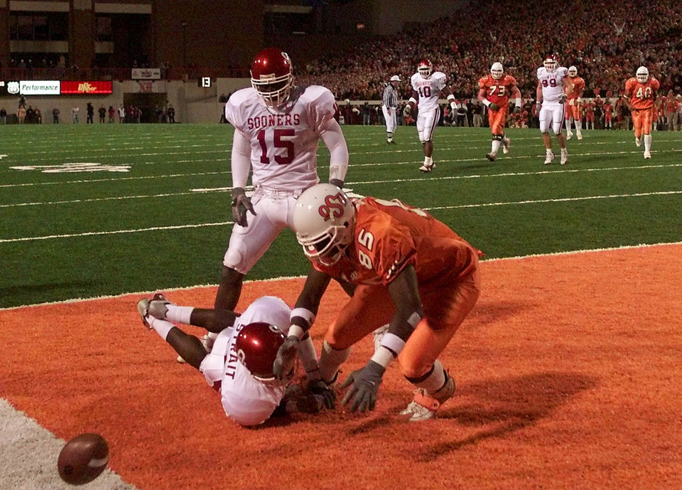 OSU's Marcellus Rivers falls to the turf with OU's Derrick Strait who just knocked away OSU's last chance to score on fourth down during the Bedlam college football game in Stillwater, Okla. Nov. 25, 2000. Covering also for OU was J. T. Thatcher. OU won, 12-7. Staff Photo by Doug Hoke.