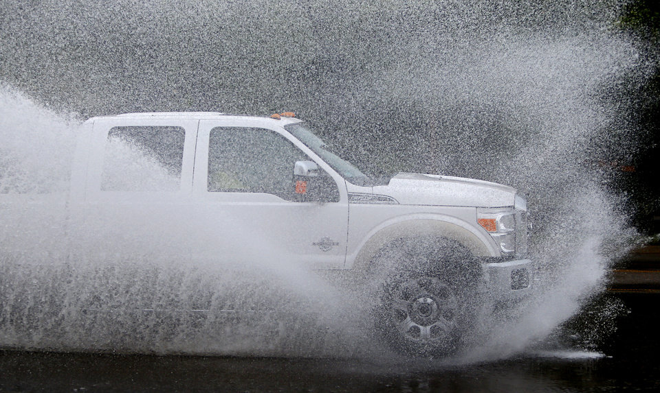 A truck splashes water as it drives through a puddle after a storm in The Village, Okla., Saturday, August 18, 2012. Photo by Bryan Terry, The Oklahoman