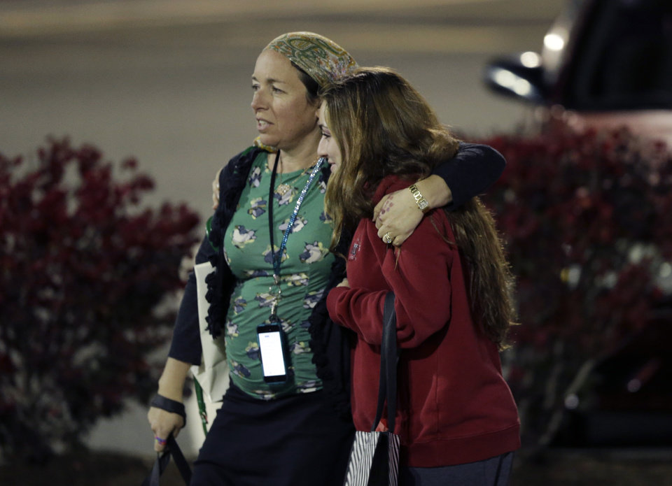 Photo - Two women walk in the parking lot of the Garden State Plaza Mall with officials standing guard following reports of a shooter, Monday, Nov. 4, 2013, in Paramus, N.J. Hundreds of law enforcement officers converged on the mall Monday night after witnesses said multiple shots were fired there. (AP Photo/Julio Cortez)