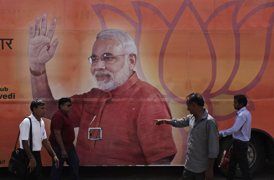 Photo - Indians walk past a bus with a photograph of India's main opposition Bharatiya Janata Party (BJP)'s prime ministerial candidate Narendra Modi as the same is prepared for celebrations anticipating his election victory in Ahmadabad, India, Thursday, May 15, 2014. Official results are expected on Friday, but exit polls by at least six major Indian TV stations show the BJP is likely to win enough seats to form a coalition government. (AP Photo/Ajit Solanki)