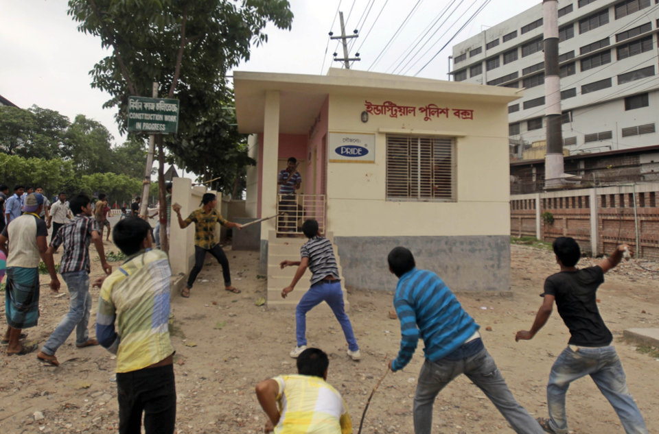 Photo - Bangladeshi garment workers throw stones and vandalize an industrial police control room during a protest against the collapse of an eight-story building that housed several garment factories and poor working conditions of the employees, in Dhaka, Bangladesh, Saturday, April 27, 2013. Police in Bangladesh took into custody five people in connection with the collapse of a shoddily-constructed building that collapsed this week, as rescue workers pulled out 19 survivors out of the rubble on Saturday and vowed to continue as long as necessary to find others despite fading hopes. (AP Photo/A.M. Ahad)