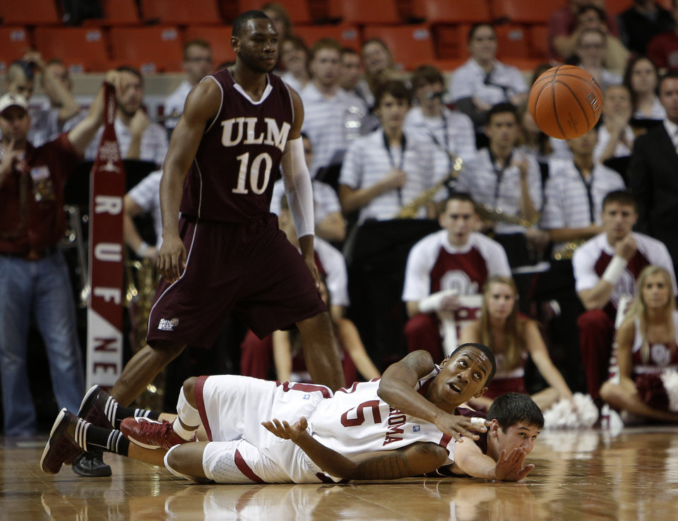 Photo - Oklahoma's Je'Lon Hornbeak (5) throws the ball away from Louisiana's Trent Mackey (5) and Amos Olatayo (10) during a men's college basketball game between the University of Oklahoma and the University of Louisiana-Monroe at the Loyd Noble Center in Norman, Okla., Sunday, Nov. 11, 2012.  Photo by Garett Fisbeck, The Oklahoman