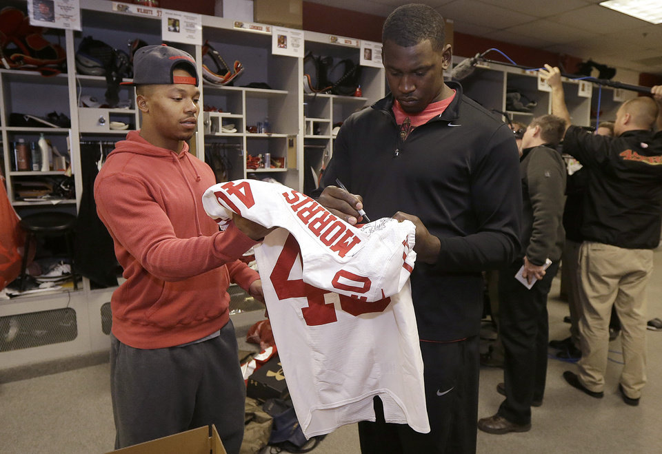 Photo - San Francisco 49ers linebacker Aldon Smith, right, signs a jersey for defensive back Darryl Morris in the locker room at an NFL training facility in Santa Clara, Calif., Monday, Jan. 20, 2014. The 49ers lost to the Seattle Seahawks in the NFC Championship Game. (AP Photo/Jeff Chiu)