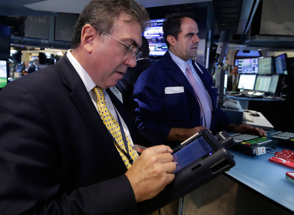 Photo - Trader John Bishop, left, works on the floor of the New York Stock Exchange Wednesday, Sept. 25, 2013. Investors continue to worry about the economy and the growing possibility of a government shutdown. (AP Photo/Richard Drew)
