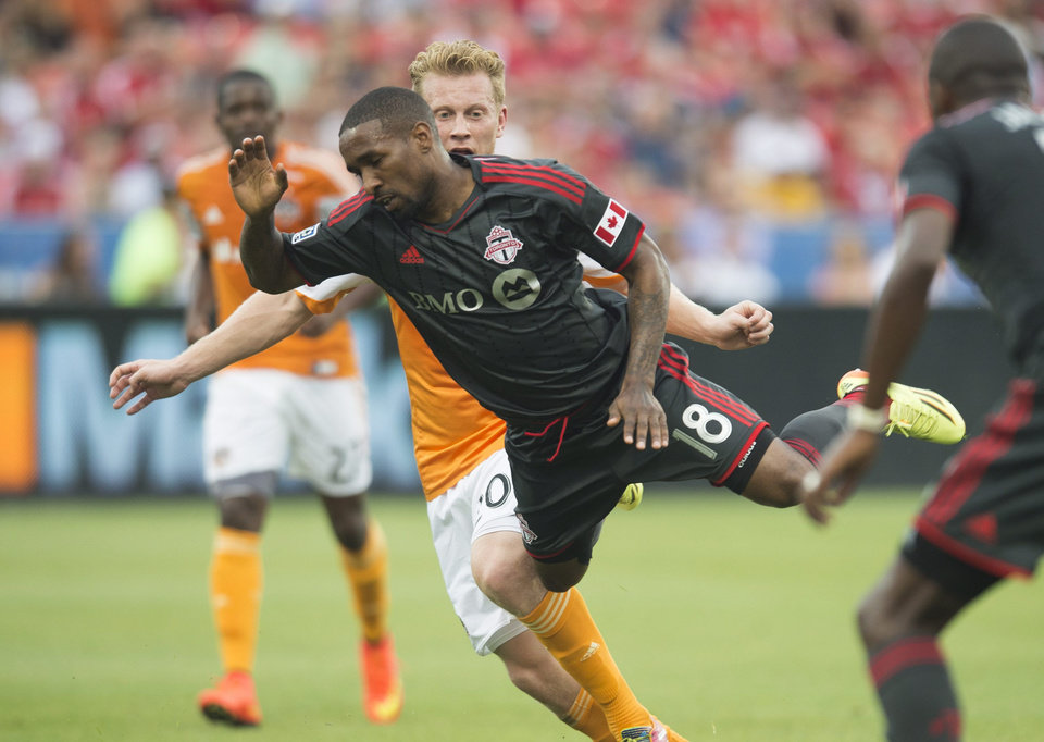 Photo - Toronto FC's Jermain Defoe, center, gets knocked off his feet by Houston Dynamo's Andrew Driver during the first half of MLS soccer action in Toronto on Saturday, July 12, 2014. (AP Photo/The Canadian Press, Darren Calabrese)