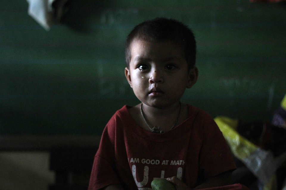 Photo - A boy waits in a temporary shelter after Typhoon Bopha made landfall in Compostela Valley in southeastern Philippines Tuesday Dec. 4, 2012. Typhoon Bopha (local name Pablo), one of the strongest typhoons to hit the Philippines this year, barreled across the country's south on Tuesday, killing at least 40 people and forcing more than 50,000 to flee from inundated villages. (AP Photo/Karlos Manlupig)