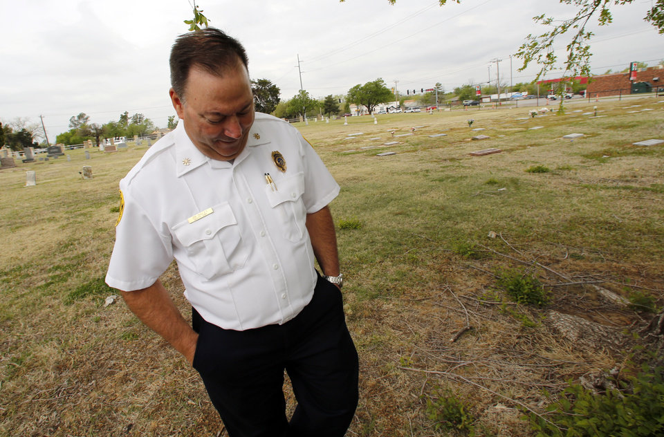 Photo -  Deputy Fire Chief Jim Bailey shows the location of a mass gravesite discovered at the IOOF Cemetery in Norman where the victims of a 1918 fire at the state mental hospitalare believed to be buried. PHOTO BY STEVE SISNEY, THE OKLAHOMAN   STEVE SISNEY -