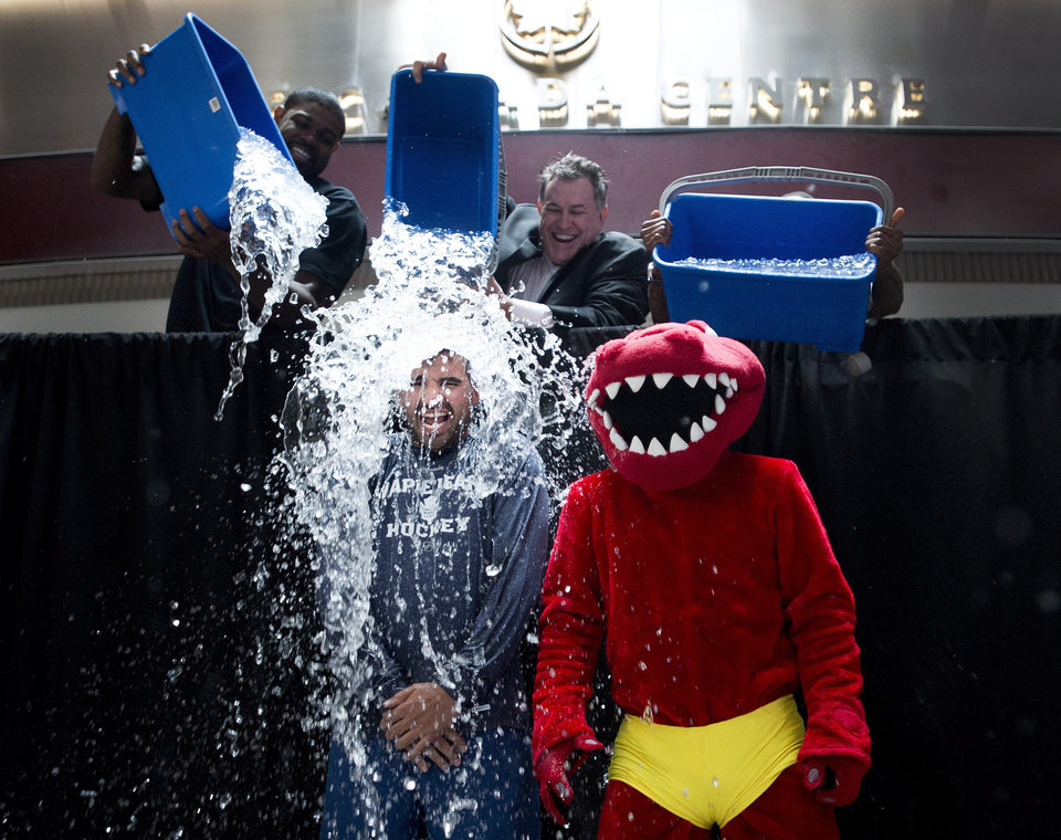 Photo - Nazem Kadri, bottom left, of the Maple Leafs and the Raptor, bottom right, participate in the ALS Ice Bucket Challenge as Jermain Defoe, top right, of Toronto FC, Amir Johnson, left, of the Toronto Raptors and Tim Leiweke, center, President and CEO of Maple Leaf Sports Entertainment dump water on them in Toronto on Wednesday, Aug. 20, 2014. (AP Photo/The Canadian Press, Nathan Denette)