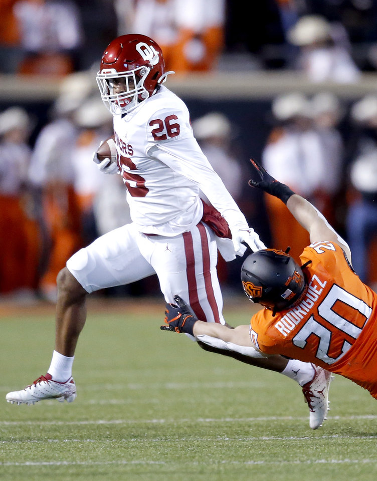 Photo - Oklahoma's Caleb Murphy (26) get by Oklahoma State's Malcolm Rodriguez (20) in the second quarter in the during the Bedlam college football game between the Oklahoma State Cowboys (OSU) and Oklahoma Sooners (OU) at Boone Pickens Stadium in Stillwater, Okla., Saturday, Nov. 30, 2019. OU won  34-16. [Sarah Phipps/The Oklahoman]