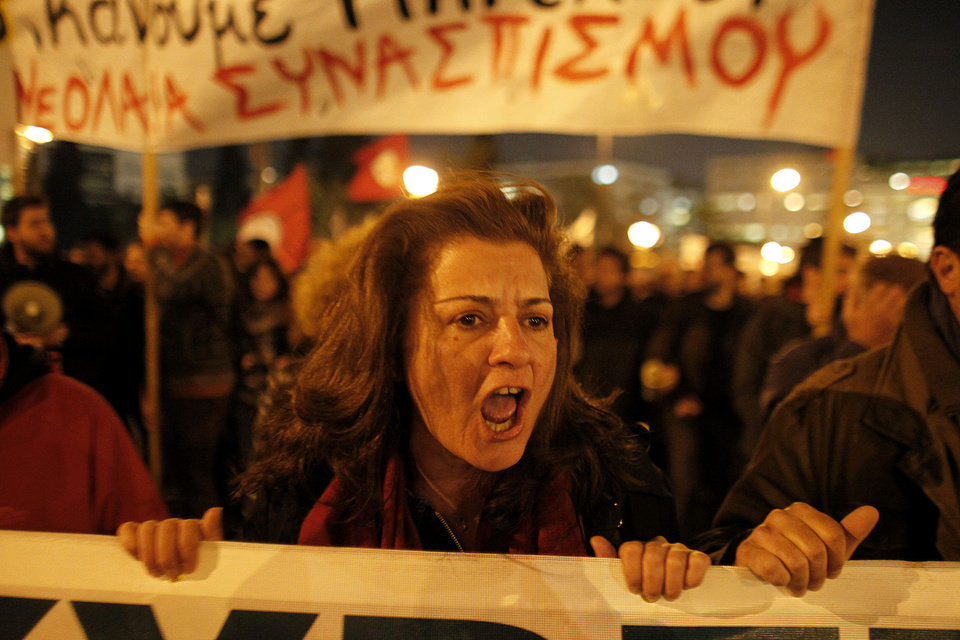 A protester chants slogans in front of the Greek Parliament during an anti austerity protest in Athens Thursday, Nov. 3 2011. Greece's embattled prime minister says he has invited opposition conservatives to join talks on a major European debt deal, ignoring calls to hold an early general election. Papandreou on Thursday insisted he never would have put the question of whether Greece stays in the joint euro currency to a popular vote. (AP Photo/Kostas Tsironis) ORG XMIT: ATH112