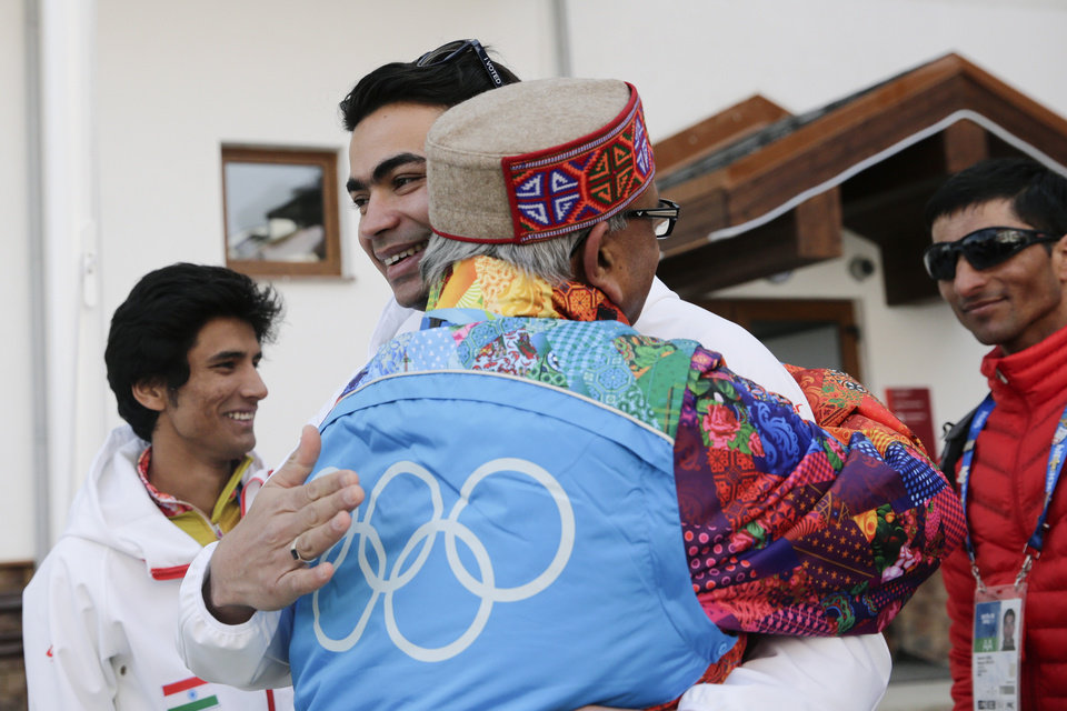 Photo - Indian luger Shiva Keshavan, center, facing camera, is hugged by supporter Omprakash Mundra after a welcome ceremony for the Indian Olympic team at the Mountain Olympic Village during the 2014 Winter Olympics, Sunday, Feb. 16, 2014, in Krasnaya Polyana, Russia. (AP Photo/Jae C. Hong)
