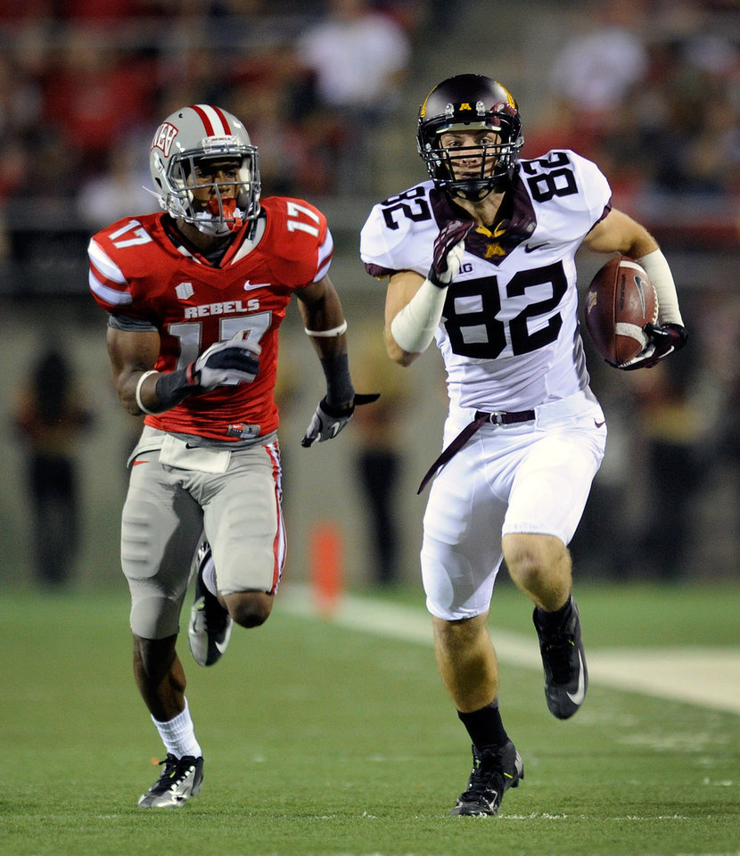 Photo -   Minnesota's A.J. Barker (82) runs down field with UNLV's Kenneth Penny (17) in pursuit during their NCAA college football game at Sam Boyd Stadium, Thursday, Aug. 30, 2012 in Las Vegas. (AP Photo/David Becker)