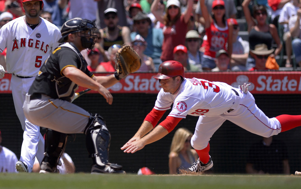 Photo - Los Angeles Angels' J.B. Shuck, right, scores on a fielder's choice by Mike Trout as Pittsburgh Pirates catcher Michael McKenry takes a late throw during the second inning of their baseball game on Sunday, June 23, 2013, in Anaheim, Calif.  (AP Photo/Mark J. Terrill)