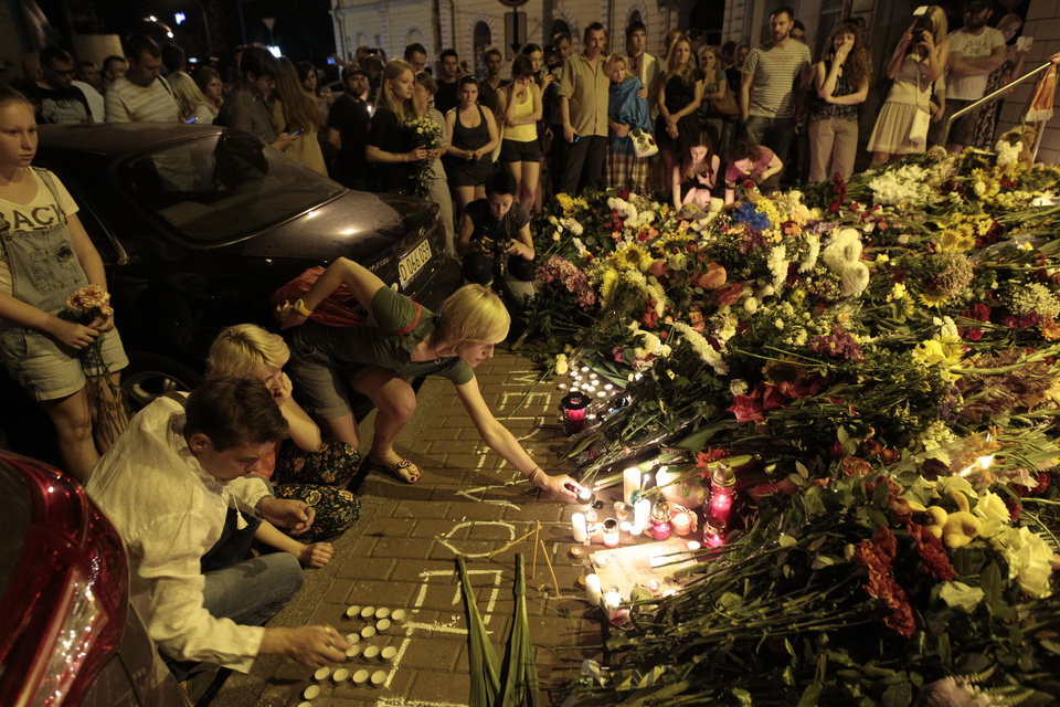 Photo - People hold candles and place flower tribute outside the Dutch embassy to commemorate victims of Malaysia Airlines plane crash in Kiev, Ukraine, Thursday, July 17, 2014.  A Malaysian Airlines passenger jet was shot down in eastern Ukraine on Thursday, and both the Ukrainian government and pro-Russian rebels blamed one another for the attack.(AP Photo/Sergei Chuzavkov)
