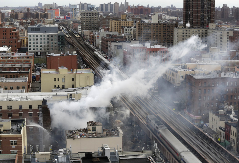 Photo - Firefighters, lower left, pour water on the site of a building explosion, as a Metro-North commuter train, right,  passes the site on Thursday, March 13, 2014 in New York.  Rescuers working amid gusty winds, cold temperatures and billowing smoke pulled four additional bodies Thursday from the rubble of two New York City apartment buildings, raising the death toll to at least seven from a gas leak-triggered explosion that reduced the area to a pile of smashed bricks, splinters and mangled metal.  The explosion Wednesday morning in Manhattan's East Harlem injured more than 60 people.  (AP Photo/Mark Lennihan)