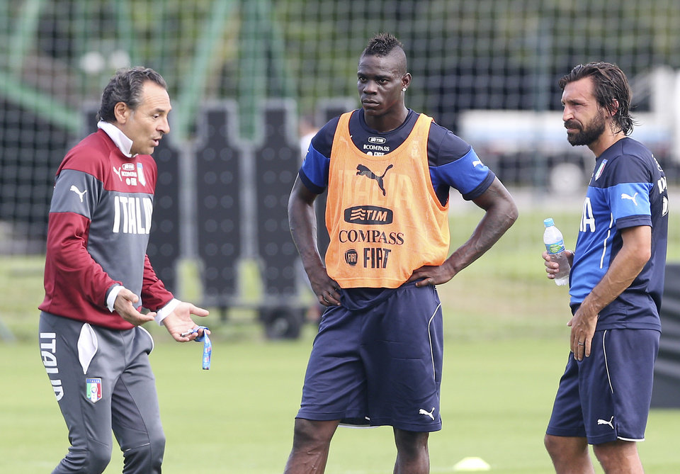 Photo - Italy's coach Cesare Prandelli, left, talks with his players Mario Balotelli, center, and Andrea Pirlo during a training session for the World Cup in Mangaratiba, Brazil, Wednesday, June 11, 2014. The international soccer tournament starts on Thursday. (AP Photo/Antonio Calanni)