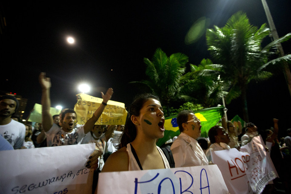 Photo - People march during an anti-government protest at Ipanema beach, in Rio de Janeiro, Brazil, Friday, June 21, 2013. Demonstrations began as an outcry against a 10-cent hike in bus and subway fares in Brazil's largest cities, but have continued even after announcements that the increases would be rescinded. Protesters have expressed frustration with corruption and what they say are high taxes and poor public services. They've demanded everything from education reforms to free bus fares while denouncing the billions of public dollars spent on stadiums before the World Cup and the Olympics. (AP Photo/Silvia Izquierdo)