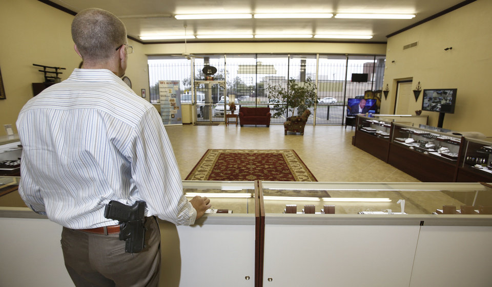 At right: Michael Butler stands guard with his gun exposed at Absolute Diamond & Gold Buyers in Oklahoma City. The business is one of several that will continue to allow its employees and customers to carry their weapon concealed Thursday but will advise against open carry. Photo by Steve Gooch,  The Oklahoman