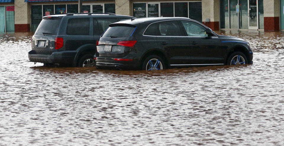 Photo - Cars sit in a flooded parking lot in Moore, Okla. on Wednesday, May 6, 2015.  Photo by Chris Landsberger, The Oklahoman