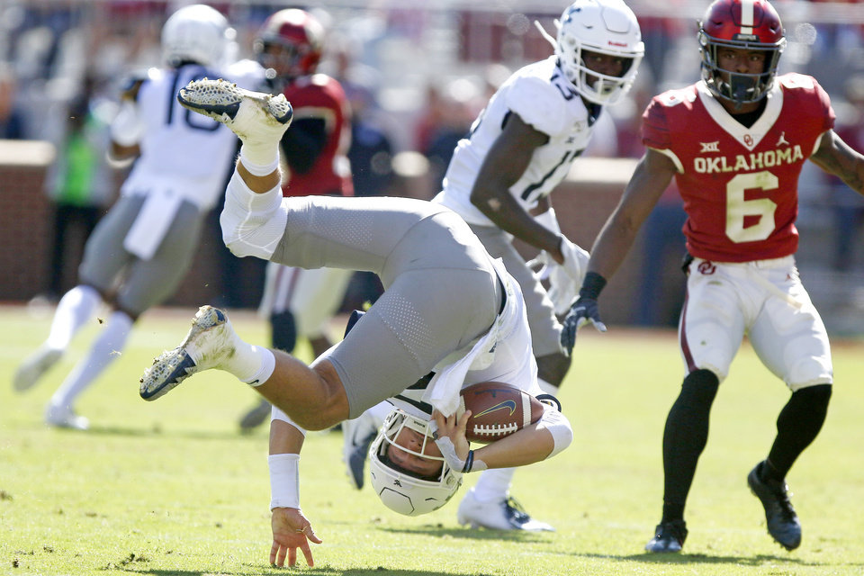 Photo - West Virginia's Austin Kendall (12) is tripped up during a college football game between the University of Oklahoma Sooners (OU) and the West Virginia Mountaineers at Gaylord Family-Oklahoma Memorial Stadium in Norman, Okla, Saturday, Oct. 19, 2019. Oklahoma won 52-14. [Bryan Terry/The Oklahoman]