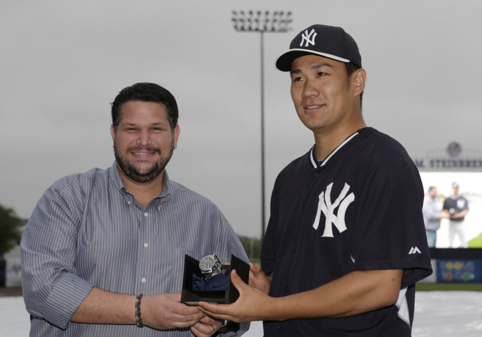 Photo - Baseball Writers Association of America representative Mark Feinsand, left, poses for a photograph with New York Yankees starting pitcher Masahiro Tanaka after presenting Tanaka with a watch after the Yankees awarded Tanaka with the 2014 James P. Dawson award, given annually to the outstanding Yankee rookie in spring training, before a spring exhibition baseball game in Tampa, Fla., Saturday, March 29, 2014. Saturday's game against the Miami Marlins was was canceled due to rain. (AP Photo/Kathy Willens)
