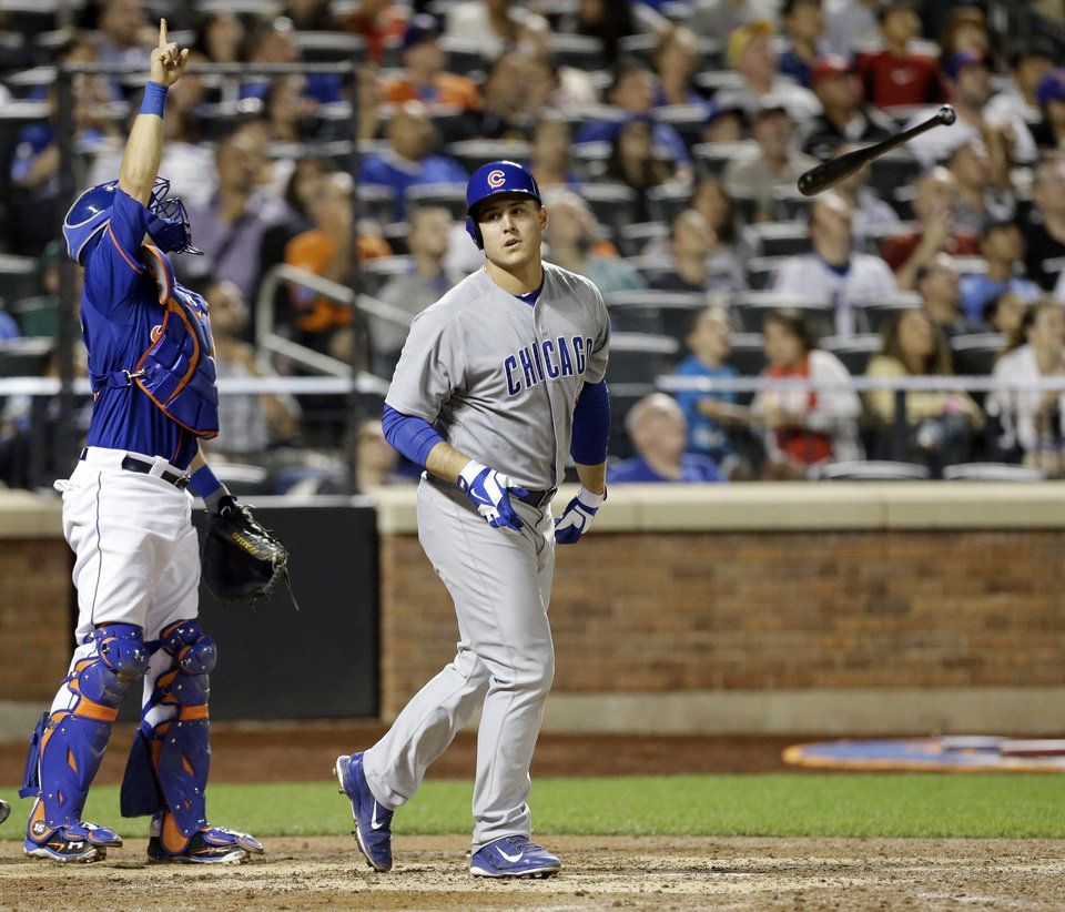Photo - Chicago Cubs' Anthony Rizzo, right, tosses his bat after hitting a pop fly as New York Mets catcher Travis d'Arnaud points to the ball during the seventh inning of a baseball game Saturday, Aug. 16, 2014, in New York. (AP Photo/Frank Franklin II)