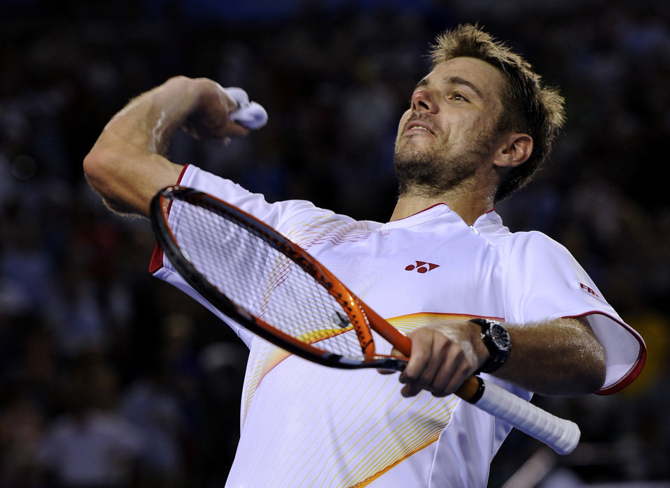 Photo - Stanislas Wawrinka of Switzerland throws his wristband to the spectators after defeating Tomas Berdych of the Czech Republic during their semifinal at the Australian Open tennis championship in Melbourne, Australia, Thursday, Jan. 23, 2014.(AP Photo/Andrew Brownbill)