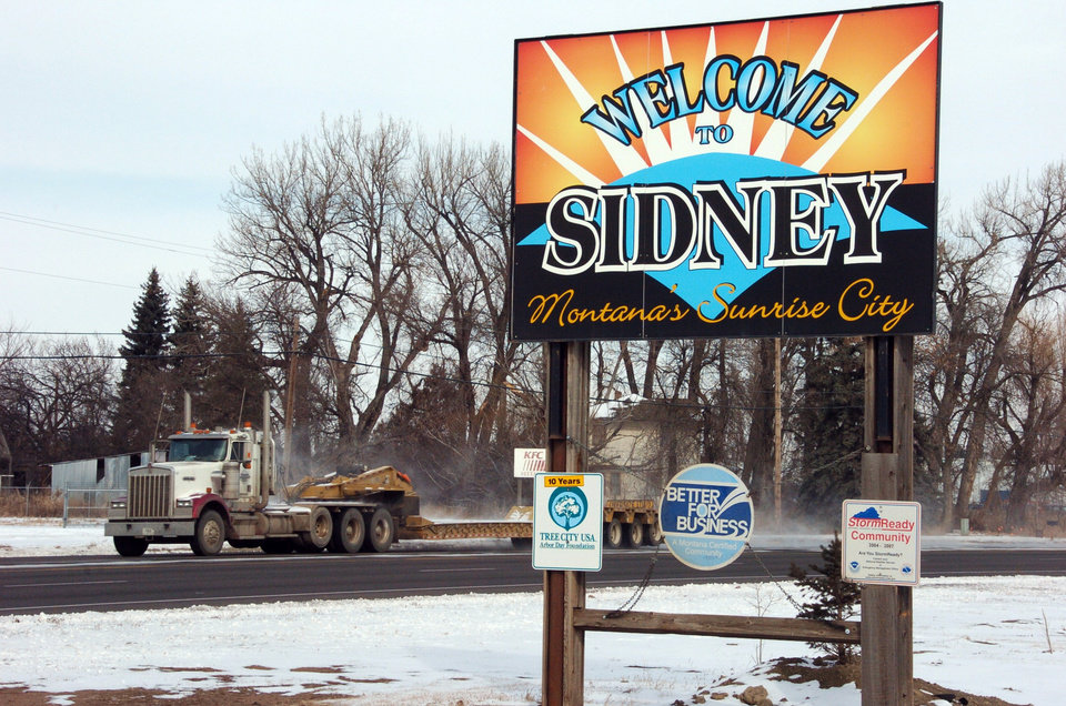 This Feb. 28, 2012 photo shows a truck driving by the welcome sign for Sidney, Mont. Sidney is experiencing a boom spurred by companies seeking to extract oil from the massive Bakken formation beneath western North Dakota and eastern Montana. More than 16 million barrels of crude are now being pumped every month from the massive Bakken oil field beneath eastern Montana. But Sidney\'s new-found prosperity doesn\'t dull the sting of the recent kidnapping and apparent murder of a local teacher, Sherry Arnold, who authorities allege was snatched from a Sidney street by two men among the thousands in search of their own slice of the boom\'s multi-billion-dollar payoff. (AP Photo/Matthew Brown)