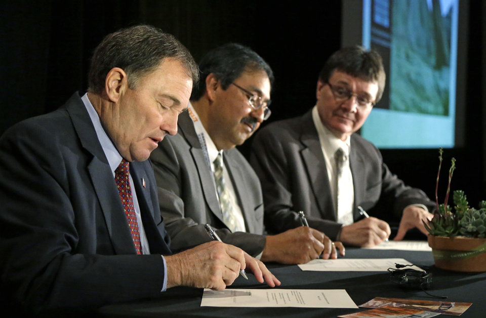 Photo - From left to right, Utah Gov. Gary Herbert kicks off his first annual Outdoor Recreation Summit by signing a long-awaited swap of state and federal lands in Grand, San Juan and Uintah Counties, with state Bureau of Land Management Director Juan Palma and state trust lands director Kevin Carter Thursday, May 8, 2014, in Salt Lake City. The deal gives the federal government about 25,000 acres of conservation and recreation lands in exchange for about 35,000 acres of energy-rich land for the state.  (AP Photo/Rick Bowmer)