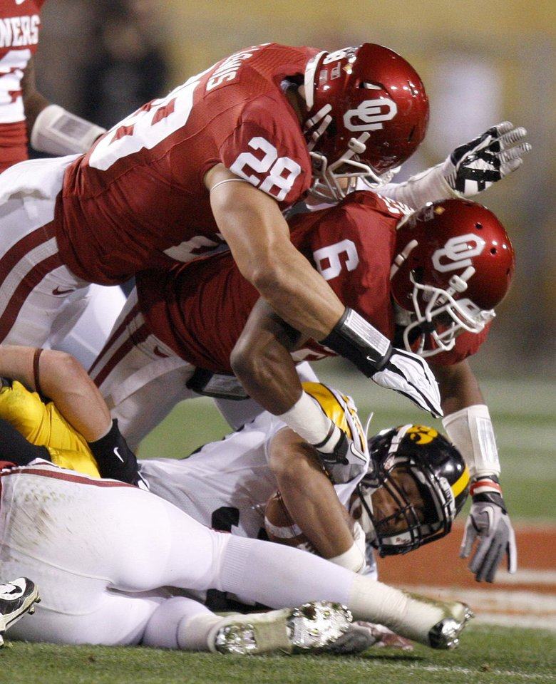 Photo - Oklahoma's Travis Lewis (28) and Demontre Hurst (6) bring down Iowa's Jordan Canzeri (33) during the Insight Bowl college football game between the University of Oklahoma (OU) Sooners and the Iowa Hawkeyes at Sun Devil Stadium in Tempe, Ariz., Friday, Dec. 30, 2011. Photo by Bryan Terry, The Oklahoman
