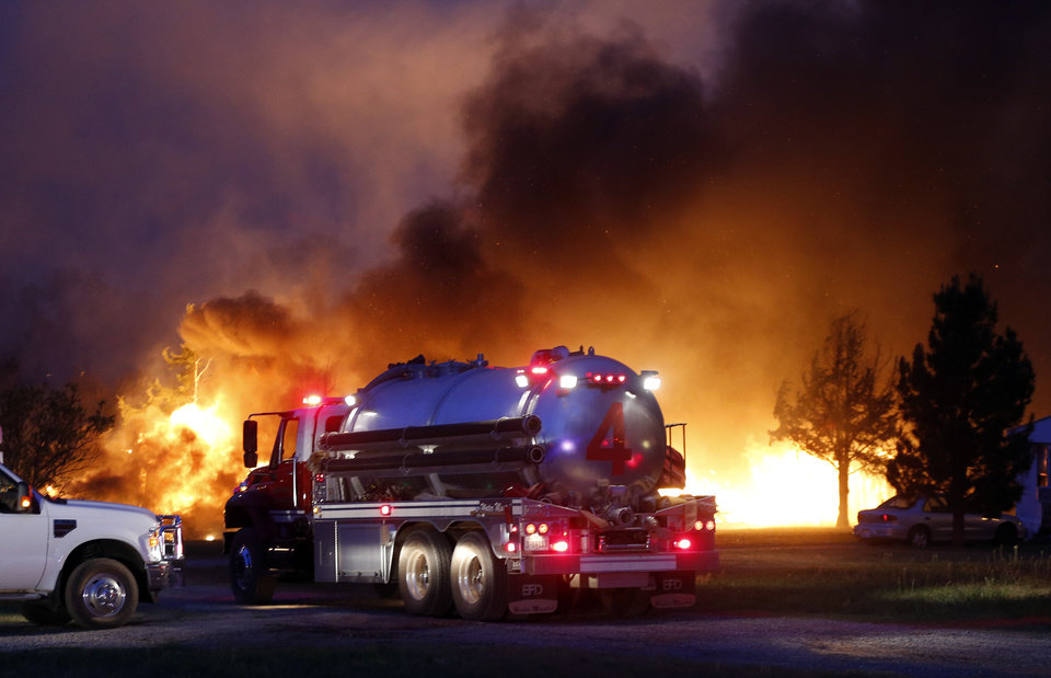 Photo - A water tanker arrives as fires burn at a mobile home park near Prairie Grove Rd. and Douglas during wildfires in Logan County, Sunday, May 4, 2014. Photo by Nate Billings, The Oklahoman