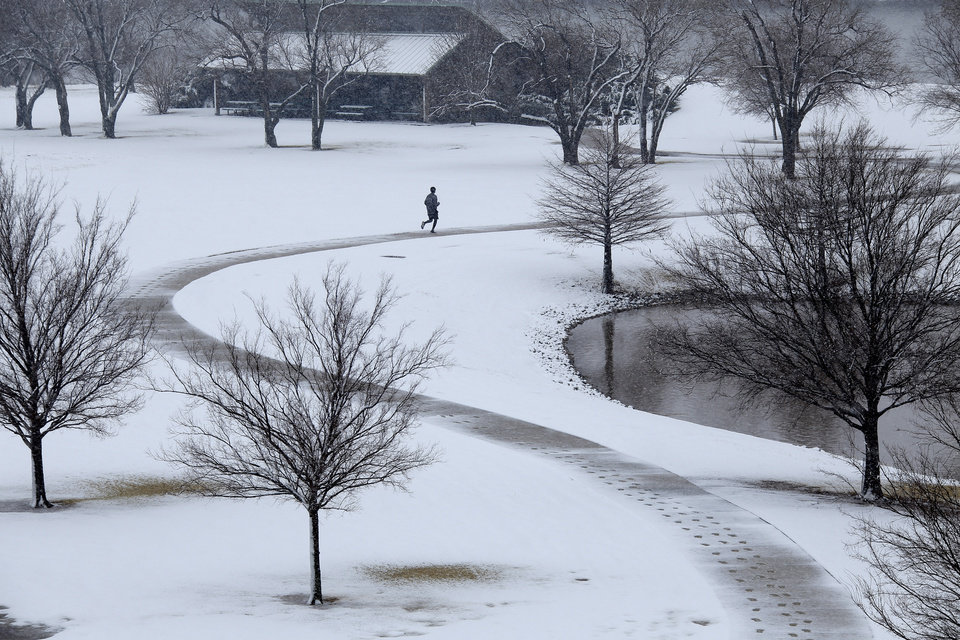Photo - A lone jogger makes his way around a pond near Britton Road and I-235 during the noon hour Tuesday February 12, 2013 in Oklahoma City. Photo by Doug Hoke, The Oklahoman