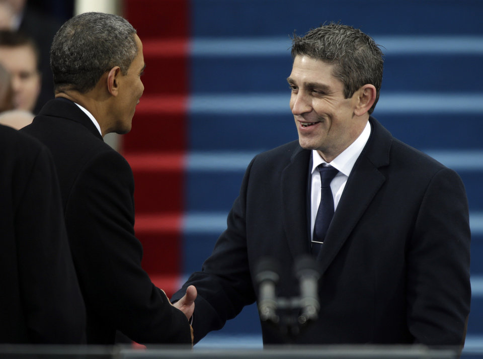 Photo - President Barack Obama, left, shakes hands with poet Richard Blanco during the ceremonial swearing-in West Front of the U.S. Capitol during the 57th Presidential Inauguration in Washington, Monday, Jan. 21, 2013. (AP Photo/Pablo Martinez Monsivais)