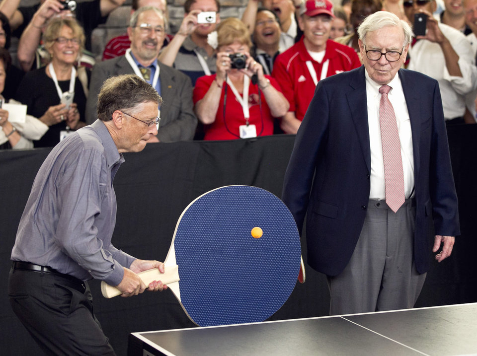 Photo - FILE - In this May 6, 2012 file photo, Warren Buffett, chairman and CEO of Berkshire Hathaway, right, watches Bill Gates use an oversize paddle as they play doubles against table tennis prodigy Ariel Hsing in Omaha, Neb. Members of the economic elite are looking for ways to reduce the nation's growing income inequality for a variety of reasons, from self-interest to pangs of conscience. Buffet advocated for a progressive estate tax before members of Congress, saying in 2007,
