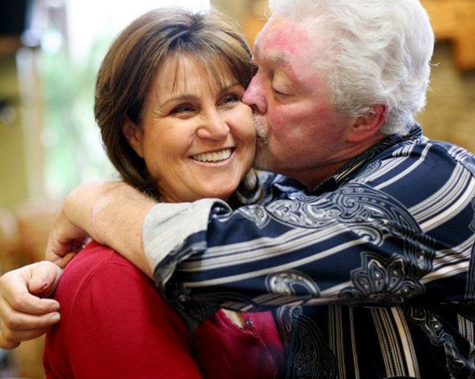 Richard Edwards kisses his wife, Cindy Edwards, in their Edmond home. Cindy Edwards asked a doctor if surgeons could replace her husband's severely burned and deformed hands. Richard said he never hesitated to receive donor hands, despite substantial risks. <strong>John Clanton</strong>